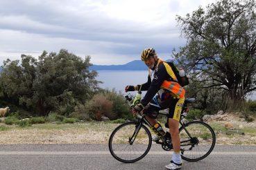 cicliste e pecore sulla strada costiera più bella Grecia Occidentale