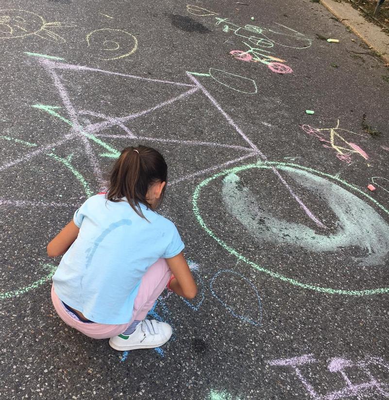 bambina disegna bicicletta con gessetti in strada chiusa al traffico a milano